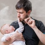 A father is smoking next to his baby